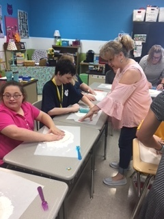 Students utilizing motor skills to roll out their dough