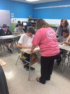 Mrs. Lewis providing instruction to a student.