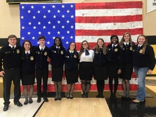 FFA students who organized the program and a flag that was created by Ms. Kelli Snell and the entire student body.